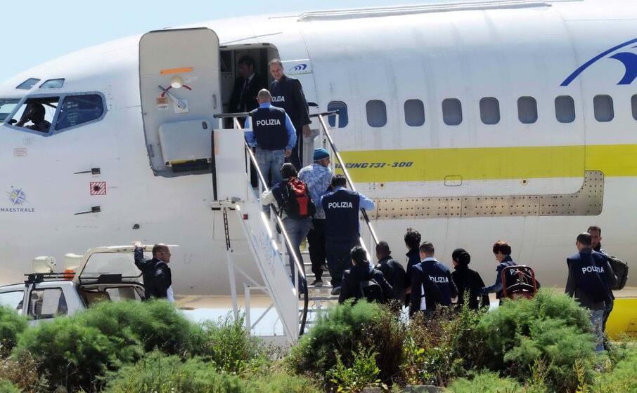 polizia scorta dei migranti su un volo per il rimpatrio (foto ansa)