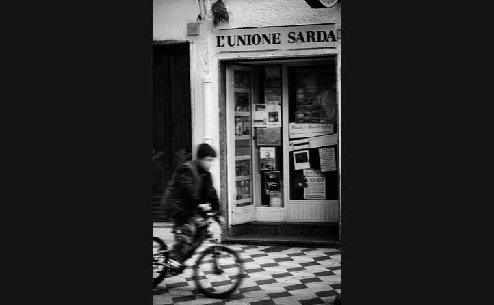 nel bellissimo scatto di _andreameloni_ un iconica immagine da sant antioco un edicola storica sullo sfondo mentre un bimbo in bicicletta sfreccia fra le vie del paese