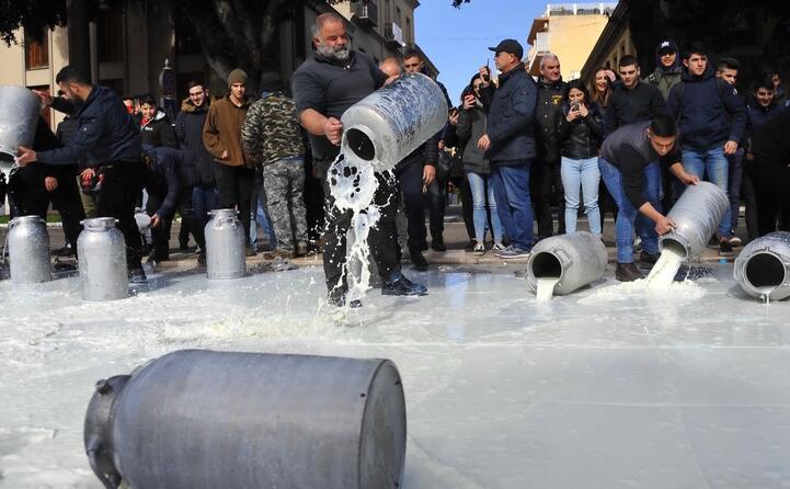 pastori gettano latte nella fontana di piazza roma a oristano