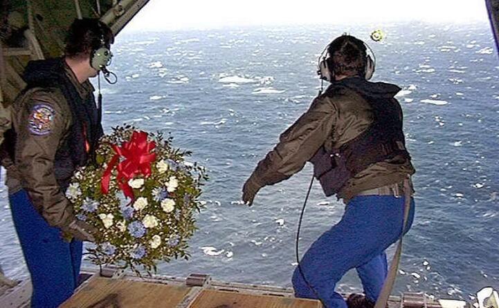 soldati gettano fiori in mare per le vittime del disastro