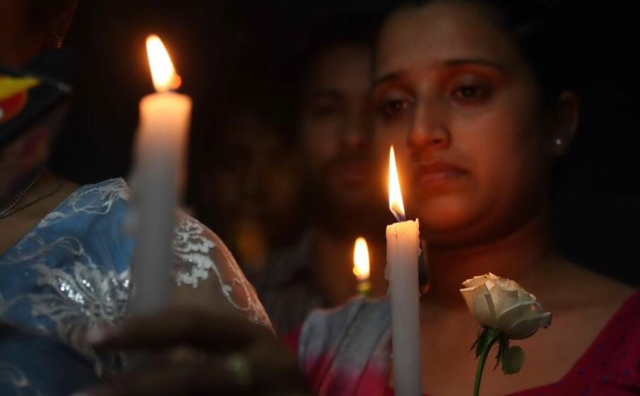 donna in lacrime alla fiaccolata per le vittime