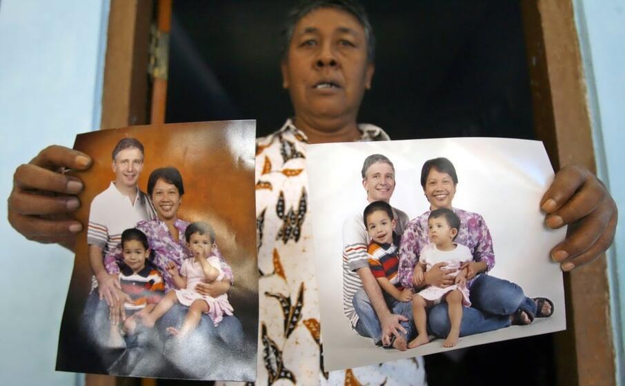 un uomo mostra le immagini dei suoi parenti morti