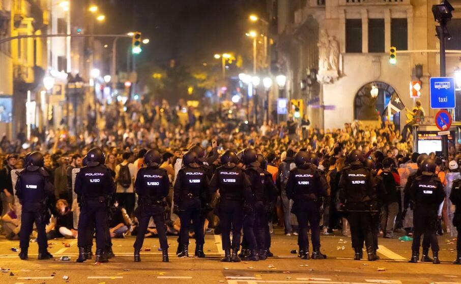 la polizia fronteggia i manifestanti a barcellona (ansa)