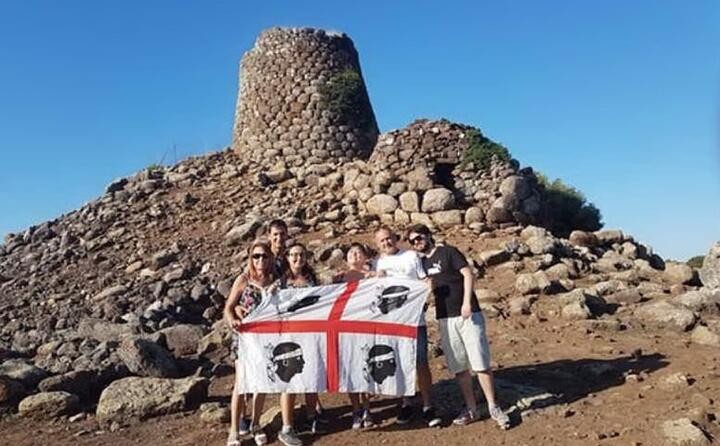 selfie di famiglia con la bandiera sarda davanti al nuraghe nuradeo a suni (foto graziella curreli)
