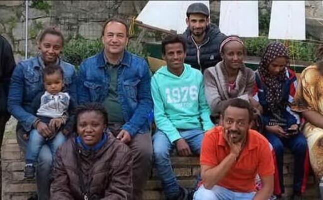 l ex sindaco lucano con alcuni rifugiati (archivio l unione sarda)