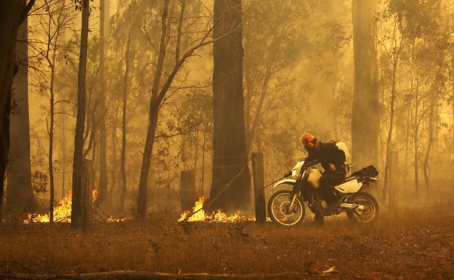 un cittadino tenta di spegnere le fiamme (ansa)
