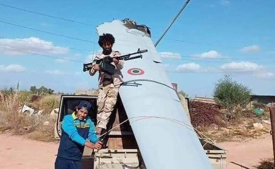 miliziani in posa con un rottame del drone in una foto circolata sul web (ansa)
