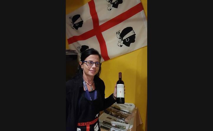 marinella mura a losone al ristorante su pastori con bandiera sarda e bottiglia di cannonau