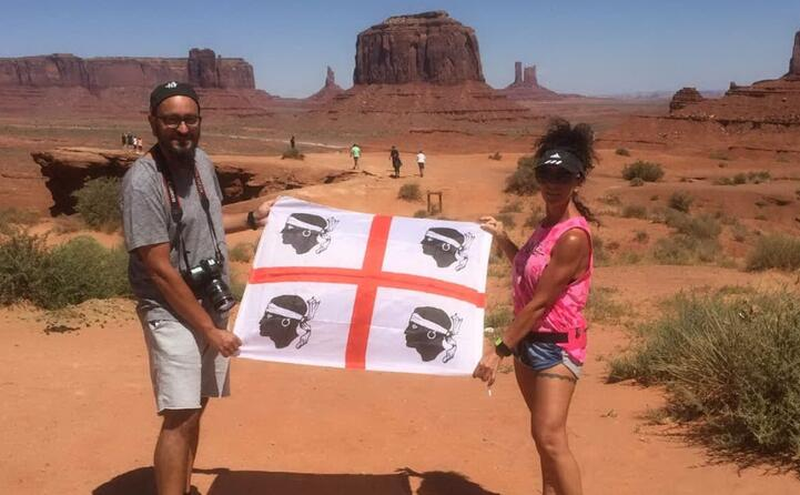 ylenia e diego in posa con la bandiera sarda alla monument valley negli usa