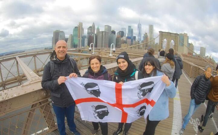 la famiglia zuddas (pa gianfranco mamma giuseppina con ilaria e giulia) da bonacardo in posa sul ponte di brooklyn con lo skyline di new york alle spalle