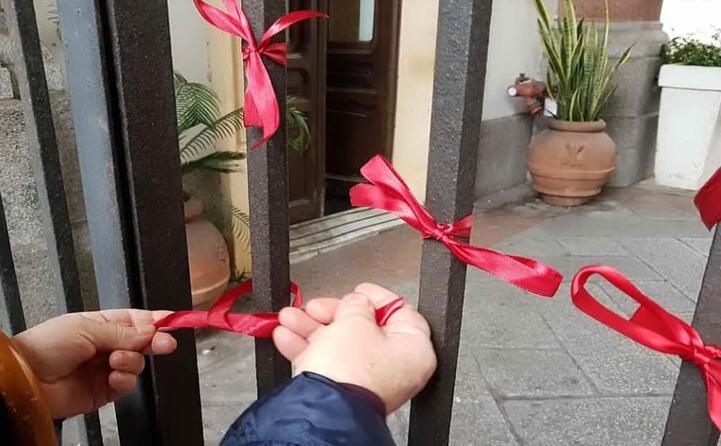 i nastrini rossi di solidariet all ingresso di palazzo civico in via roma a cagliari (foto comune di cagliari)