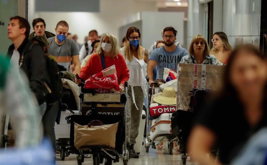 turisti con la mascherina in un aeroporto (ansa)