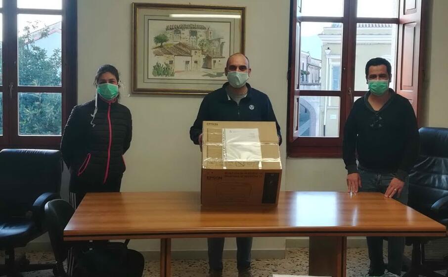 l assessore marco mandis regge il plico di mascherine ai lati gli assessori arianna porcu e francesco mameli (farris)