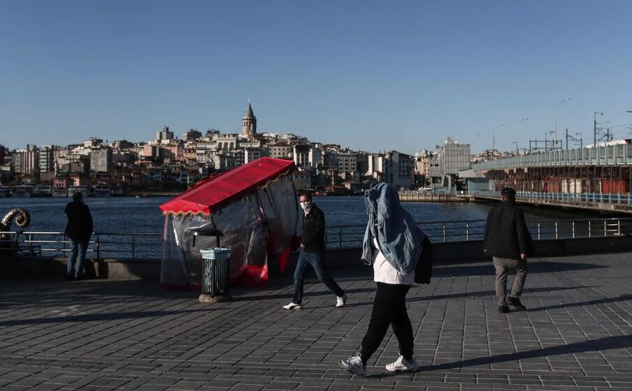 un passante si protegge con la giacca (ansa)