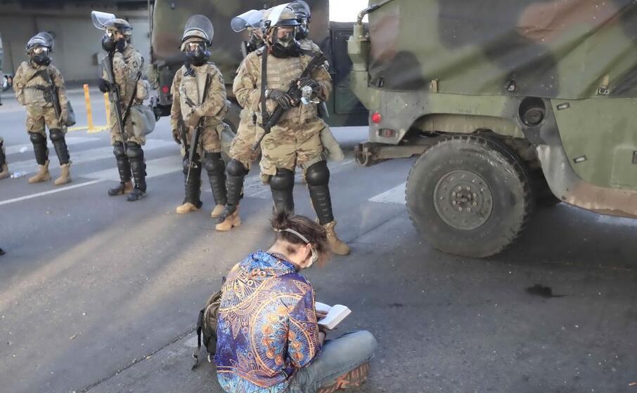 un manifestante seduto a terra davanti alla guardia nazionale (ansa maury)