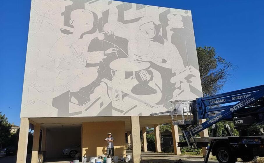 l artista millo durante la realizzazione del murale in via pascoli (foto pittau)