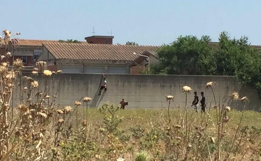 i migranti mentre scavalcano il muro (foto l unione sarda manunza)