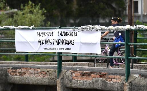 Lo striscione e le 43 rose del Comitato dei parenti delle vittime (Ansa)