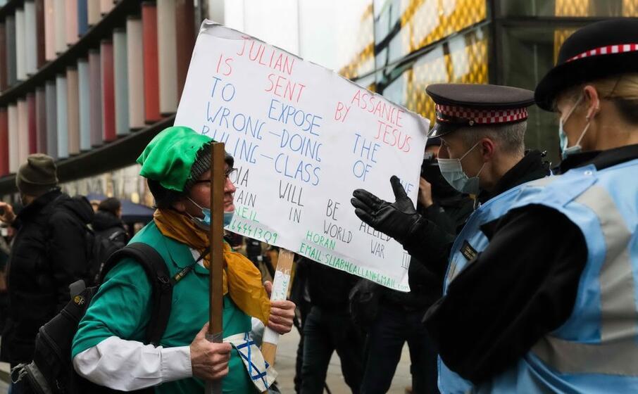 un manifestante con un cartello parla con i poliziotti