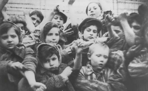 Bimbi mostrano ad Auschwitz i loro numeri tatuati dopo la liberazione dei sovietici (foto via Ansa)